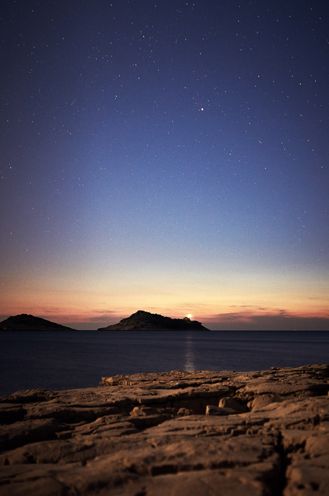 when the night coming just the lighthouse and the stars brighten the darkness